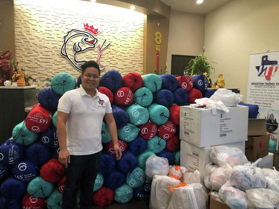 Vo Hoai Trung, founder of the organization Houston Thong Tin and owner of Alief Vietnamese restaurant Bun Cha Ca Da Nang, pauses for a moment on Monday, Nov. 26, to celebrate the 250 fishcake sandwiches, 250 cakes, 100 sleeping bags, 100 tents, 30 beanies, 10 pillows and 200 pairs of gloves and socks that he and other volunteers would hand out later to homeless people in Alief and downtown Houston. In just three months, Houston Thong Tin has gained nearly 17,000 members and plans to do the charity projects on a monthly basis. Photo: Tracy Maness