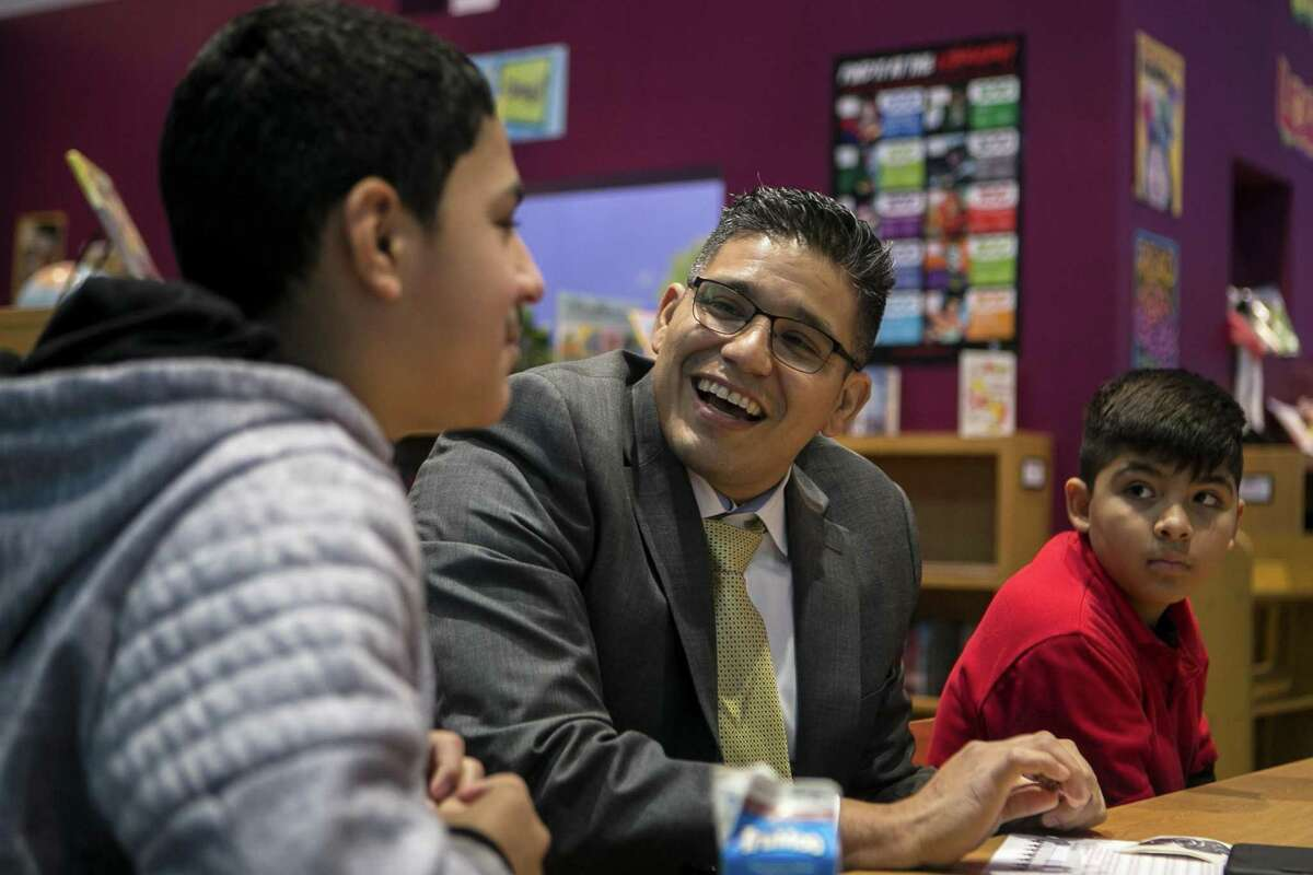 Joe Cantu, a litigation support tech specialist with the U.S. Attorney's office, laughs after Emiliano Gamez, 12, answers a question during a visit of staff members from the U.S. Attorney's office at Margil Academy Wednesday, Nov. 28, 2018. The visit was to help the ESL students gain confidence and proficiency as they practice their English.
