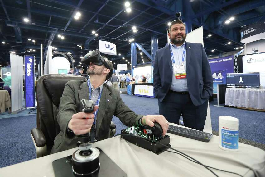James Mireles, Aviar Techology, (left) flys a F-22 Fighter Jet out of Hobby Airport using Doug Watjus, MEI Technologies' Immersive Virtual Reality simulator at the annual SpaceCom (Space Commerce Conference and Exposition) Tuesday, Nov. 27, 2018, in Houston.