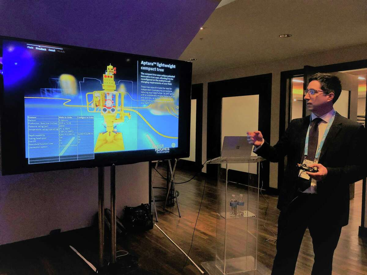 Juan Benedetti with London office of Baker Hughes uses a video game controller at a Nov. 28, 2018 event to demonstrate new technology the Houston-based oil field service company will reduce costs for offshore projects.