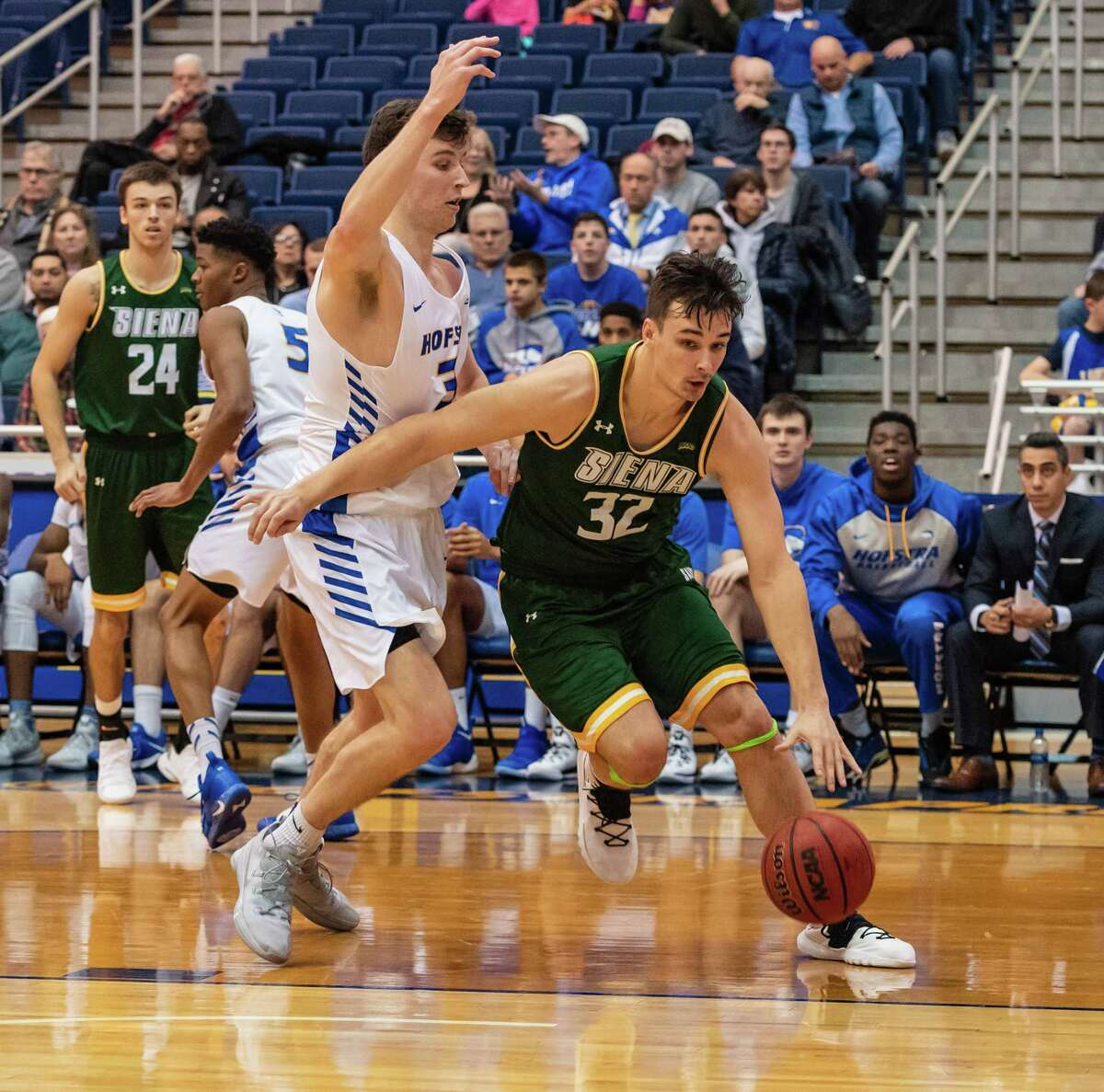 Siena forward Evan Fisher (32) drives past Hofstra forward Dan Dwyer (30) during the first half of the Siena at Hofstra men's basketball game on Wednesday, Nov. 28, 2018.