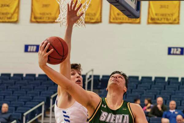 Siena forward Evan Fisher (32) looks to score on Hofstra forward Dan Dwyer (30) during the first half of their men's basketball game on Wednesday, Nov. 28, 2018.