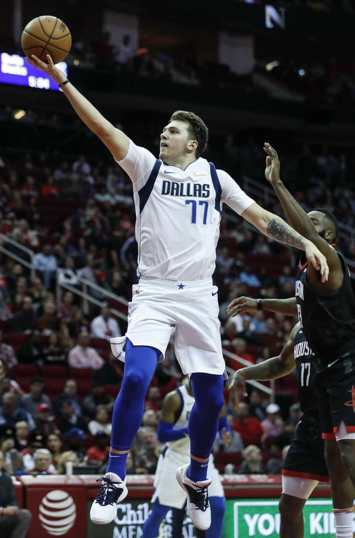 Dallas Mavericks forward Luka Doncic (77) shoots a layup after driving past Houston Rockets guard James Harden (13) during the second half of an NBA basketball game at Toyota Center on Wednesday, Nov. 28, 2018, in Houston.