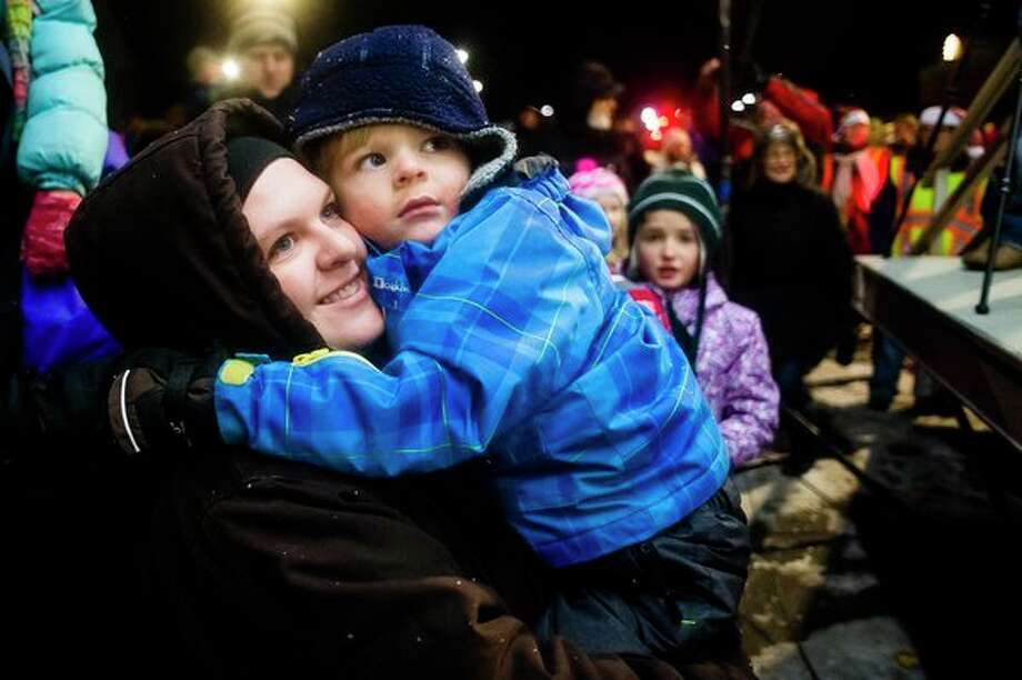 (Top) Midland residents Liz Wenger, left, and Leighton Wenger, 4, center, listen to Santa and Mrs. Claus during the annual lighting of the Midland County Courthouse on Tuesday in downtown Midland. (Left) Crowds admire the lights on the Midland County Courthouse on Tuesday in downtown Midland. (Katy Kildee/kkildee@mdn.net)