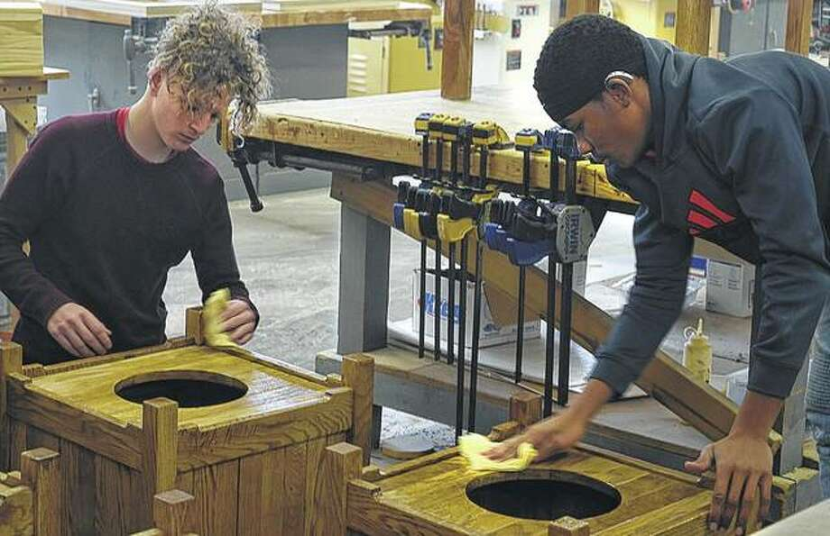 Trystan Mort (left) and James Hawkins, both juniors at the Illinois School for the Deaf, clean and polish receptacles Wednesday in preparation for delivery to the Governor's Mansion in Springfield.