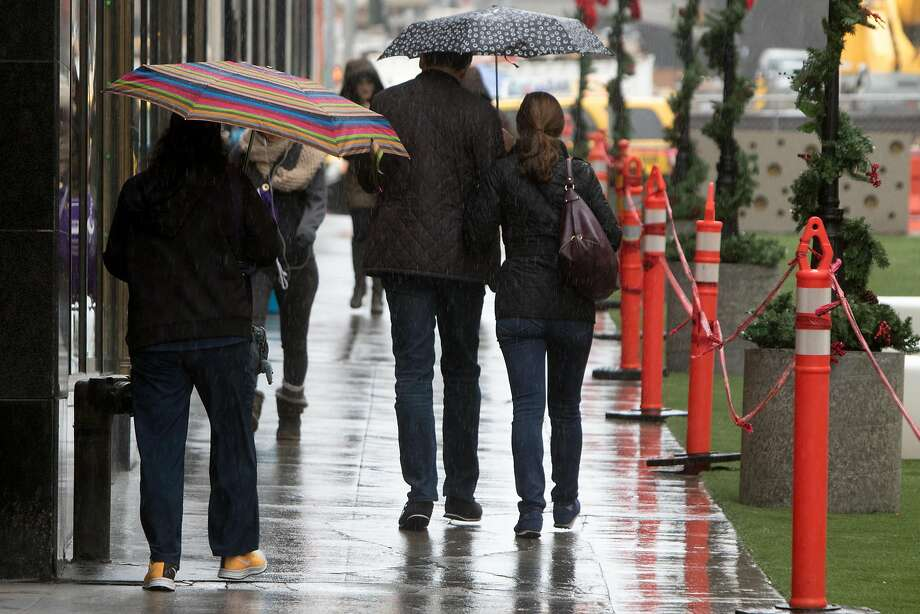 Light to moderate rain caused pedestrians in San Francisco to seek cover on Tuesday morning November 24, 2015. Photo: Douglas Zimmerman / SF Gate