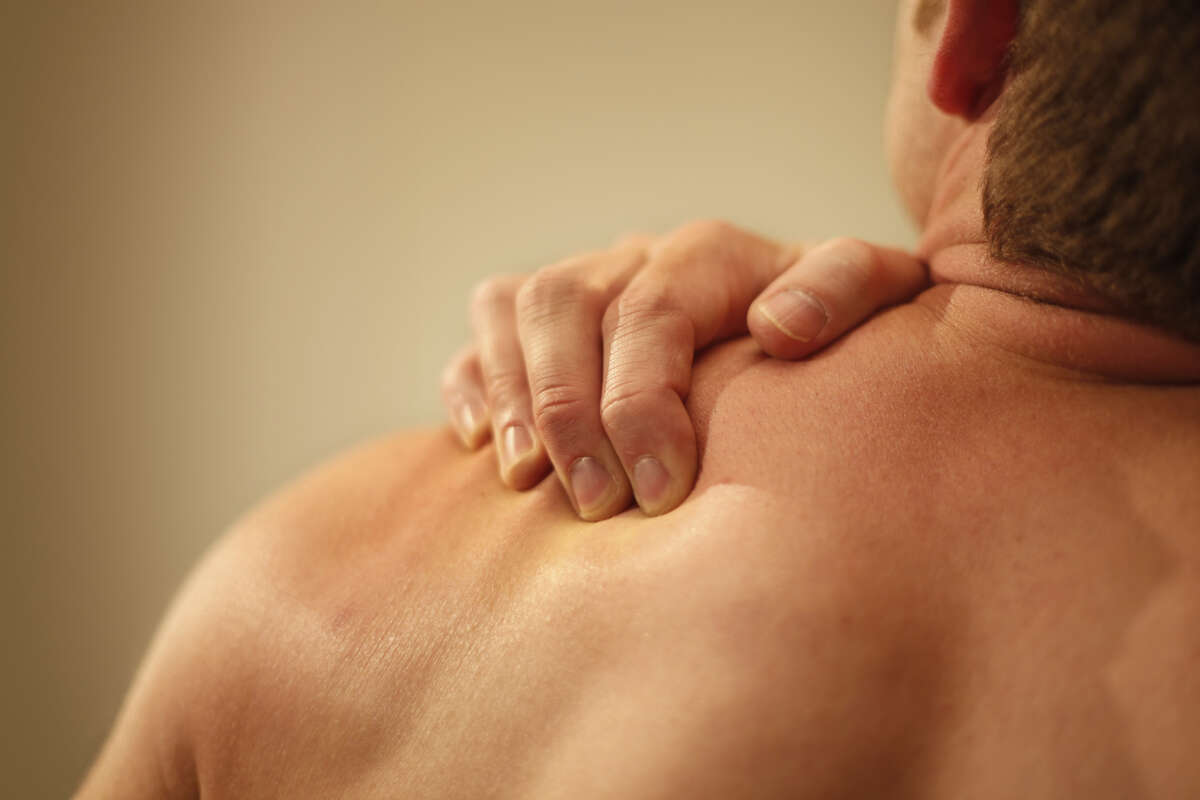 One pump of the product is applied to a man's shoulders and upper arms.