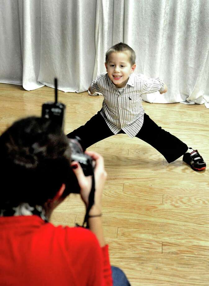 A Help-Portrait photographer shoots a 3-year-old during a free photo session. Prints are given to families for free during the holiday season. Photo: File Photo / The News-Times
