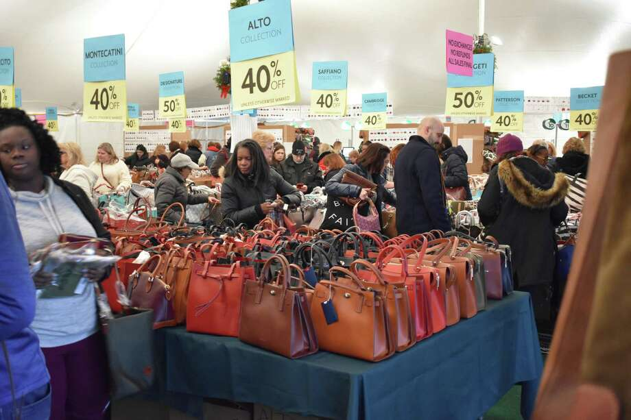 Shoppers peruse Dooney & Bourke handbags in mid-December 2017 at the company's annual tent sale in Norwalk, Conn. Photo: Alexander Soule / Hearst Connecticut Media / Stamford Advocate