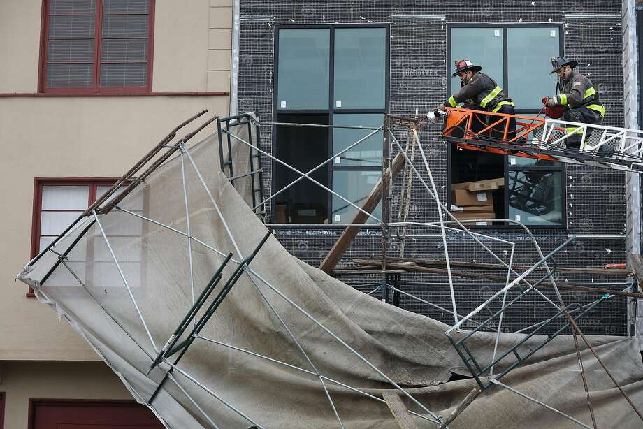 Firefighters remove pieces of scaffolding  that was blown down on Taraval Street during stormy weather on Thursday, November 29, 2018 in San Francisco, Calif. Photo: Lea Suzuki, The Chronicle