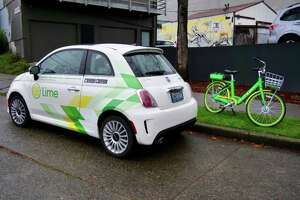 Lime is launching a new car-sharing service in Seattle powered by branded Fiat 500 cars, also known as LimePods. The company already has thousands of its green shared bikes spread across town. (GeekWire Photos / Taylor Soper)
