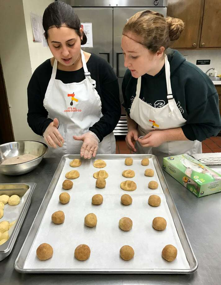 Hillary Lipper, left, makes snickerdoodles with her job coach Melissa Weaver, a senior at Sacred Heart University. Photo: Brian Koonz / For Hearst Connecticut Media Group
