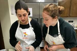 Hillary Lipper, left, makes snickerdoodles with her job coach Melissa Weaver, a senior at Sacred Heart University.