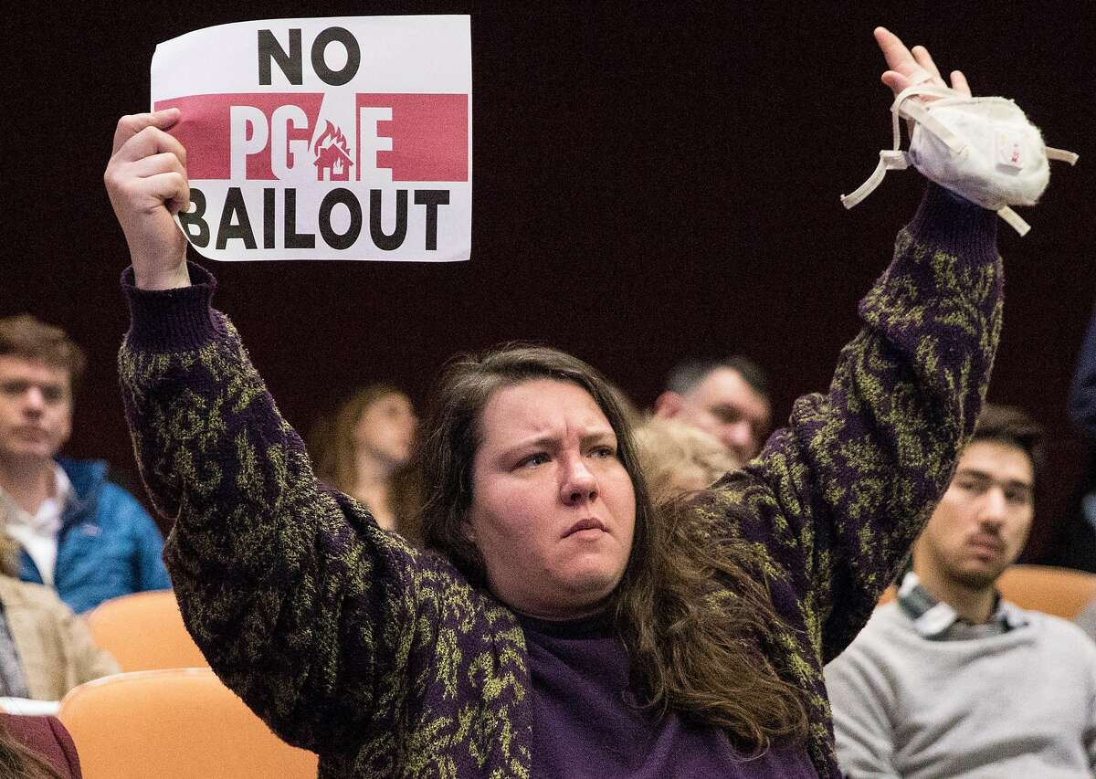 Masks Oakland founder Cassandra Williams raises her arms in protest during a California Public Utilities Commission meeting San Francisco, Calif. Wednesday, Nov. 28, 2018 surrounding the fate of PG&E following multiple deadly wildfires.