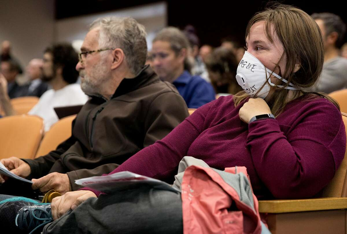 Rusty Staples (right) wears a respiratory mask in protest during a California Public Utilities Commission meeting San Francisco, Calif. Wednesday, Nov. 28, 2018 surrounding the fate of PG&E following multiple deadly wildfires.