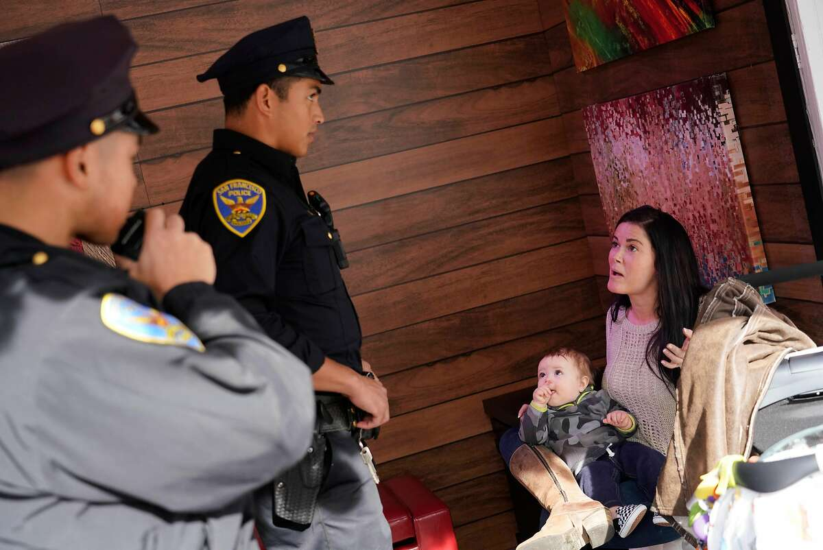 Natalie West (right) kisses her 9-month old son Seven Snodgrass (second from right), both of Eureka, as she holds him on her lap as she discusses the theft of her wallet out of her baby''s stroller with Officer Jason Castro (second from left) and Officer Gordon Wong (left) at the Union Square ice skating rink on Monday, November 26, 2018 in San Francisco, Calif.