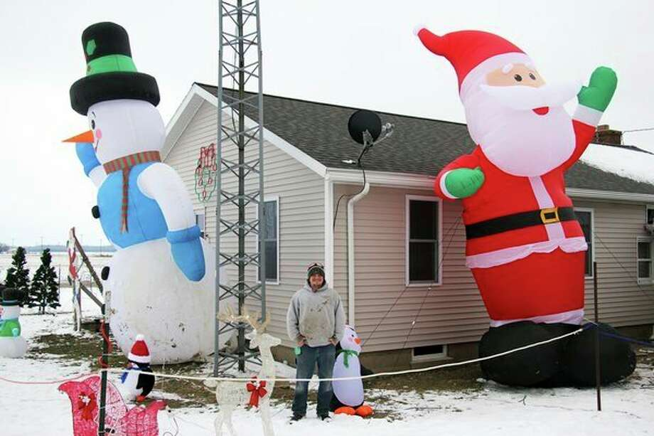 Jared Jurgess stands in front of one of the many displays he has up at his home, as part of the Jurgess Family Holiday Lighted Trail. (Seth Stapleton/Huron Daily Tribune)
