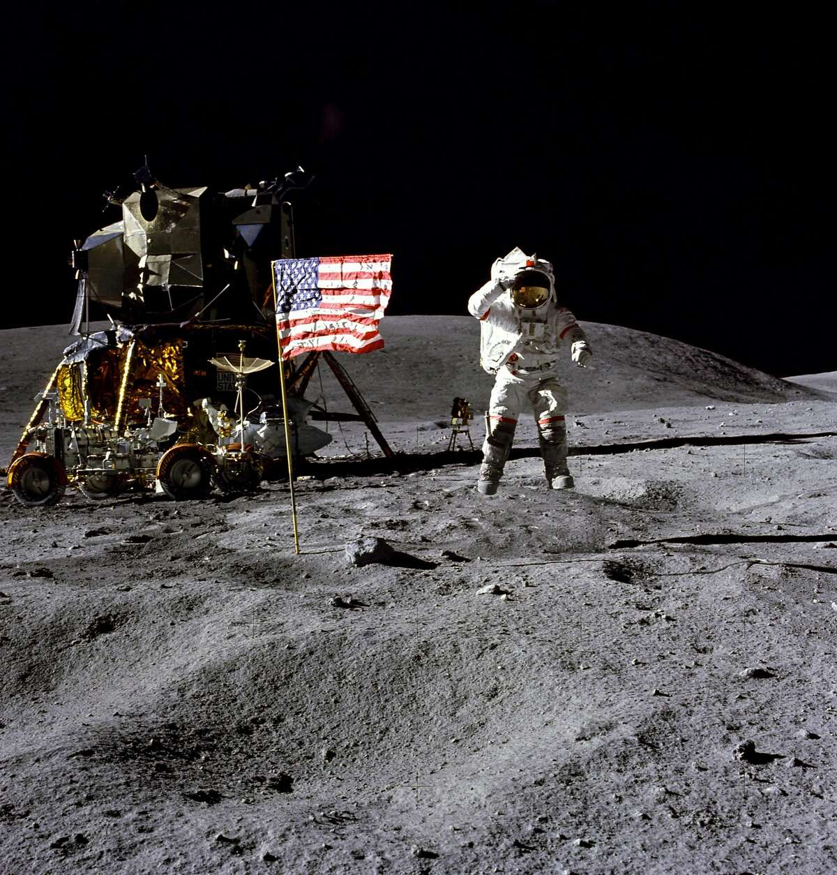 FILE- In this April 1972 photo made available by NASA, John Young salutes the U.S. flag at the Descartes landing site on the moon during the first Apollo 16 extravehicular activity. America's next moon landing will be made by private companies, not NASA. NASA Administrator Jim Bridenstine announced Thursday, Nov. 29, 2018, that nine U.S. companies will compete in delivering experiments to the lunar surface.