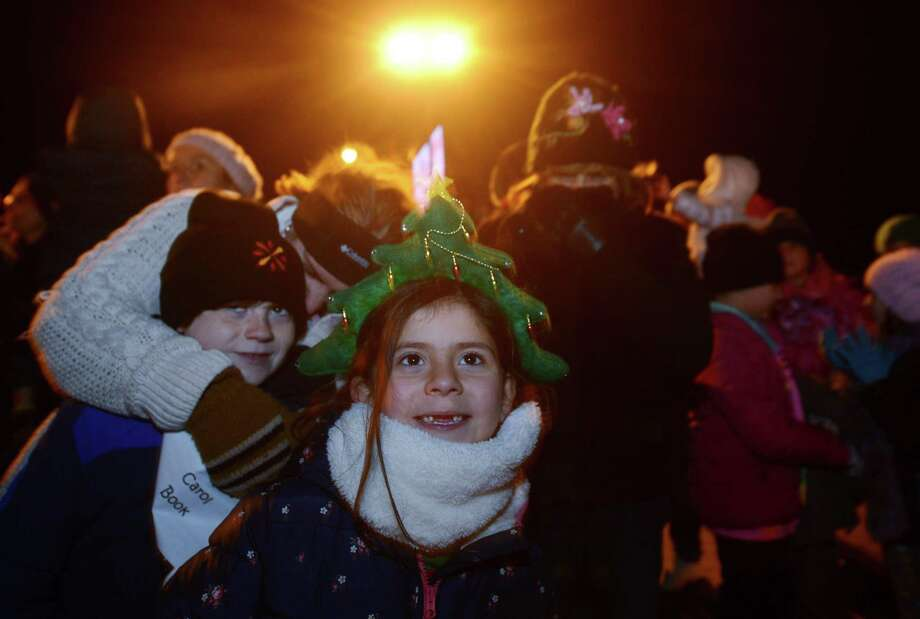 Carly Ramos, 6, of Fairfield enjoys the Christmas carols during Stew Leonard's annual Christmas Tree Lighting celebration on Tuesday at the store in Norwalk. The festivities began with plenty of musical entertainment and ended with Santa spending the evening mingling with children and handing out candy canes. For the third year, a 30-foot artificial evergreen tree will serve as the Norwalk store's holiday centerpiece. Created by American Christmas, Inc., the tree is hand-crafted by seven people over the course of a month. Once at Stews, it took 15 people more than 11 hours to put it up and string more than 33,000 LED multi-color lights. The artificial tree can be recycled at the end of its 6-year lifespan. Photo: Erik Trautmann / Hearst Connecticut Media / Norwalk Hour