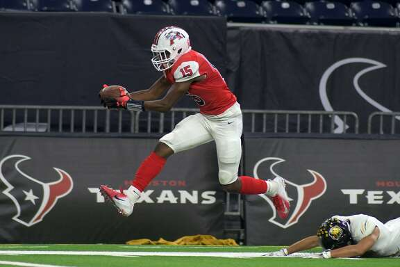 Atascocita junior wide receiver Darius Edmonds (15) tries to reach the end zone on his pass reception against a fallen Hastings defender late in the 2nd quarter of their Class 6A Div. I Region III Area Playoff matchup at NRG Stadium in Houston on Nov. 24, 2018.