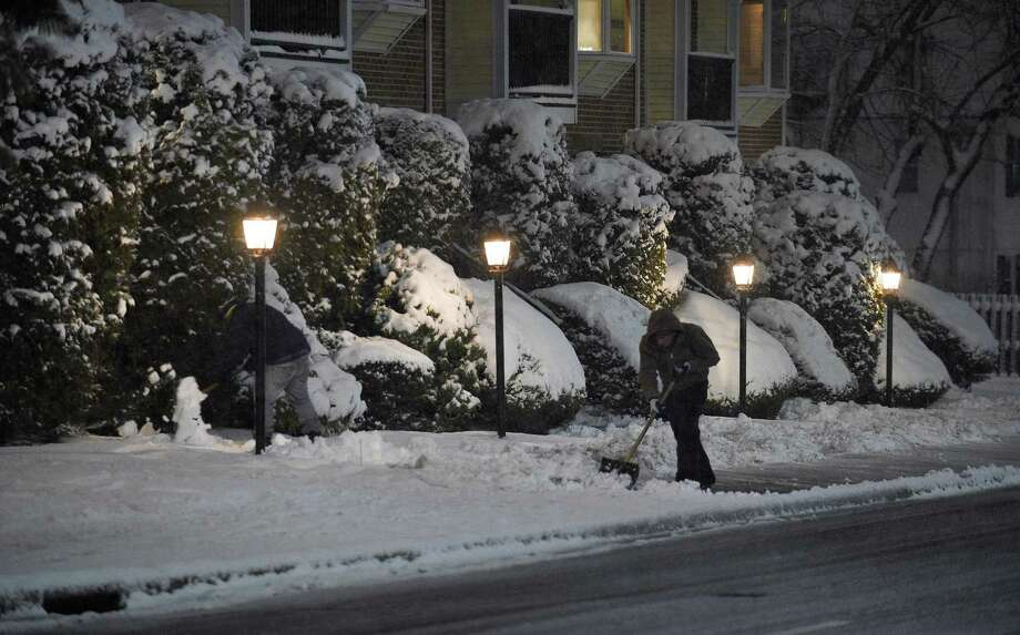 Workers clear the sidewalks along Grove Street as snow continues to fall during the overnight hours from a spring nor'easter passing through on March 21. Photo: Matthew Brown / Hearst Connecticut Media / Stamford Advocate