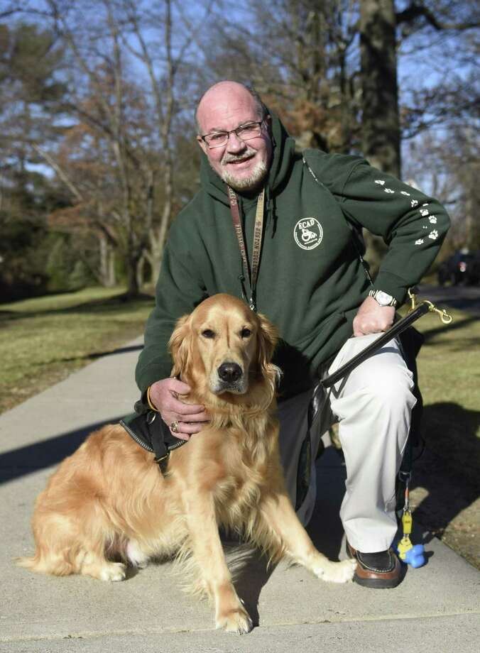 "Tom Griffen poses with his service dog, Sterling, after the ""Canines Assisting in Health"" program at Greenwich Hospital in Greenwich, Conn. Thursday, Nov. 29, 2018. Greenwich Hospital held a program teaching health care professionals how to interact with people who have service dogs, and how not to, in hospitals, medical facilities and doctor's offices. Photo: Tyler Sizemore / Hearst Connecticut Media / Greenwich Time"