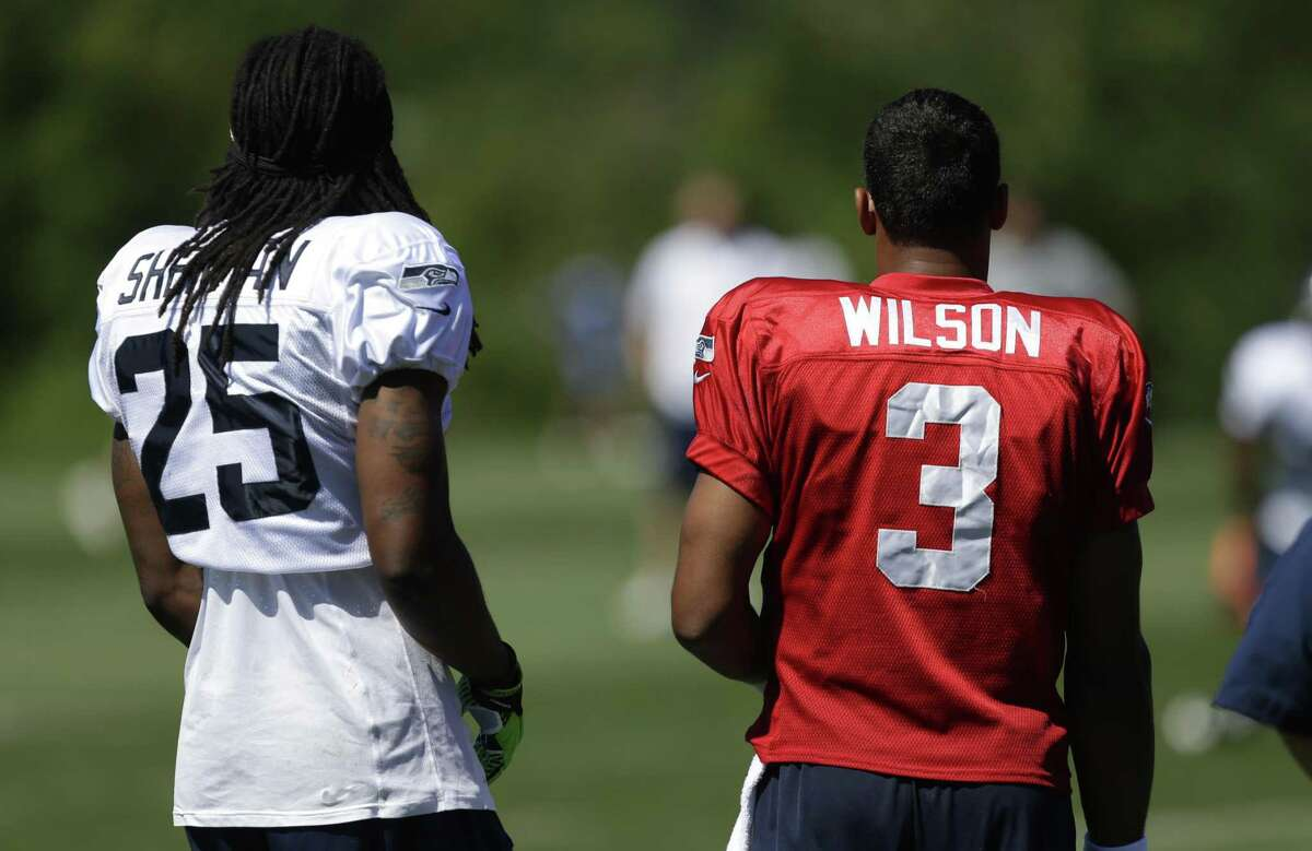 Seattle Seahawks quarterback Russell Wilson (3) and cornerback Richard Sherman (25) watch practice during NFL football training camp, Saturday, July 27, 2013, in Renton, Wash. (AP Photo/Ted S. Warren)
