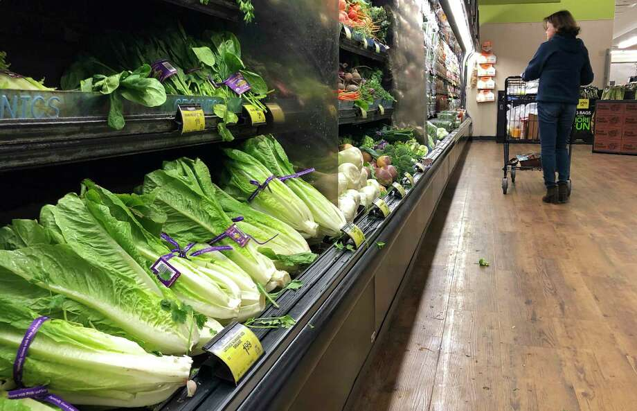 FILE - In this Nov. 20, 2018 file photo, romaine lettuce sits on the shelves as a shopper walks through the produce area of an Albertsons market in Simi Valley, Calif.  After repeated food poisoning outbreaks linked to romaine lettuce, the produce industry is confronting the failure of its own safety measures in preventing contaminations. The latest outbreak underscores the challenge of eliminating risk for vegetables grown in open fields and eaten raw. It also highlights the role of nearby cattle operations and the delay of stricter federal food safety regulations.  (AP Photo/Mark J. Terrill, File) Photo: Mark J. Terrill / Copyright 2018 The Associated Press. All rights reserved.