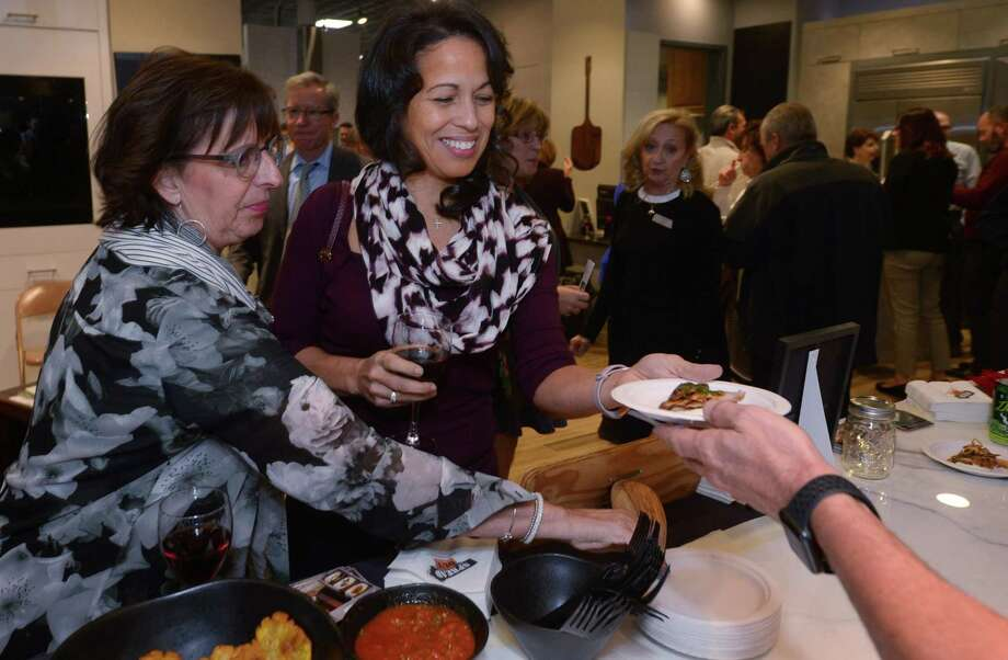 Sharon Kurtzman of Norwalk and Yvette Edgecome of Westport enjoy pork tenderloin from The Spread during the 2nd Annual Cooking for Charity Thursday, November 29, 2018, at Aitoro Appliance in Norwalk, Conn. Guests were able to sample food and beverages served by local restaurants chefs cooking right in Aitoro's showroom kitchens. Proceeds benfit the Human Services Council and the Norwalk Rotary Club. There was an amazing selection of Chance Auction Items that total over $5,000. Photo: Erik Trautmann / Hearst Connecticut Media / Norwalk Hour