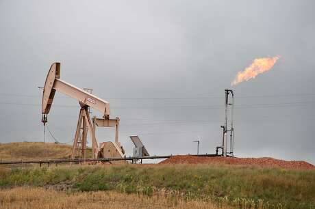 (FILES) In this file photo taken on September 6, 2016 shows pump jacks and a gas flare  near Williston, North Dakota. - Oil prices gained November 29, 2018 after the US benchmark slid below $50 a barrel following reports Russia could join a production cut at next month's OPEC meeting. The gains in petroleum prices came on a mixed day for global stocks as traders worldwide weighed Federal Reserve comments that were widely seen as dovish on monetary policy. (Photo by Robyn BECK / AFP)ROBYN BECK/AFP/Getty Images