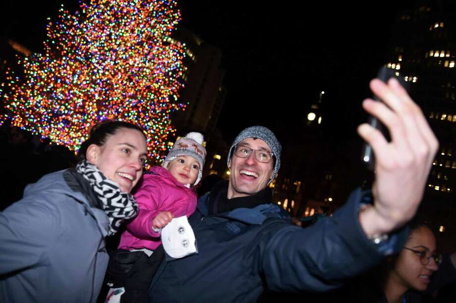 Liesbeth Juchtmans, left, of New Haven takes a selfie with her daughter, Laure Ovaere-Juchtmans, and husband, Martem Ovaere, in front of the Christmas tree on the New Haven Green after it was lit Thursday. See a photo slideshow from the tree lighting at nhregister.com. Photo: Arnold Gold / Hearst Connecticut Media / New Haven Register