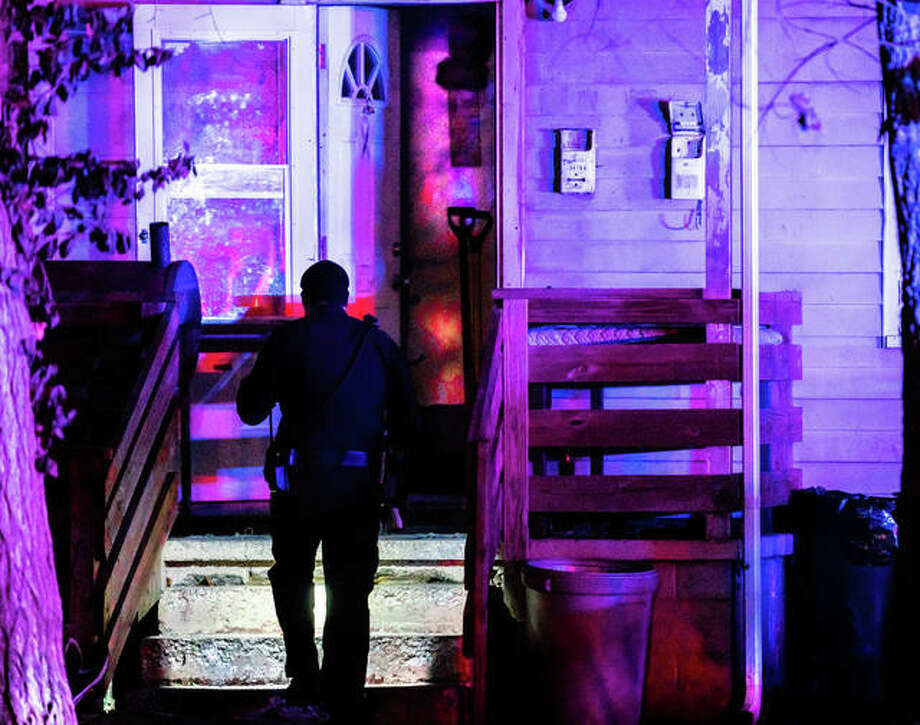 An Alton police officer shines his flashlight into the open door of a residence in the 3400 block of Boliver Street Thursday night, where authorities responded to what quickly turned into the scene of a homicide investigation. Photo: Nathan Woodside | The Telegraph