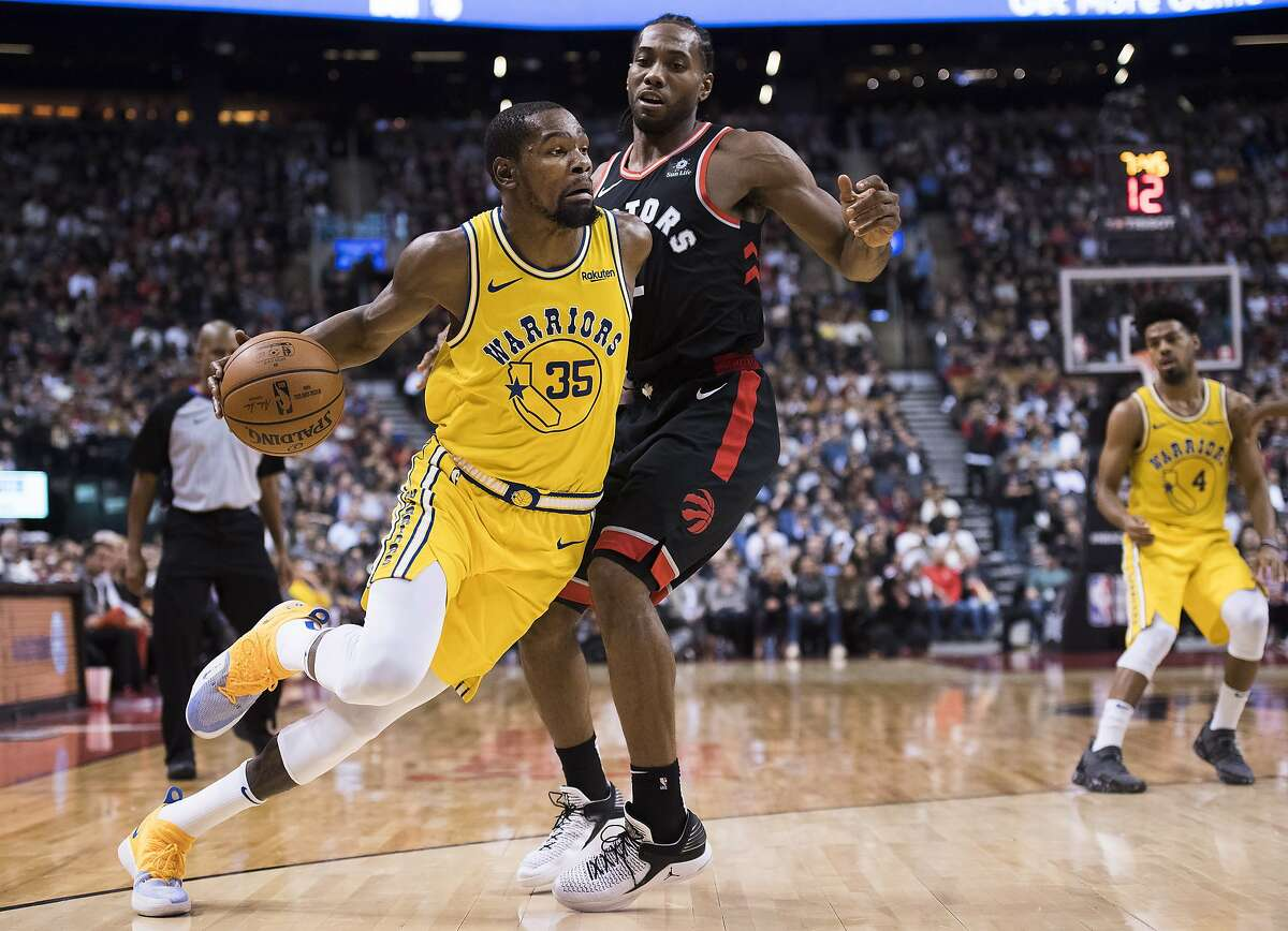 Golden State Warriors forward Kevin Durant (35) drives around Toronto Raptors forward Kawhi Leonard (2) during the second half of an NBA basketball game Thursday, Nov. 29, 2018, in Toronto. (Nathan Denette/The Canadian Press via AP)