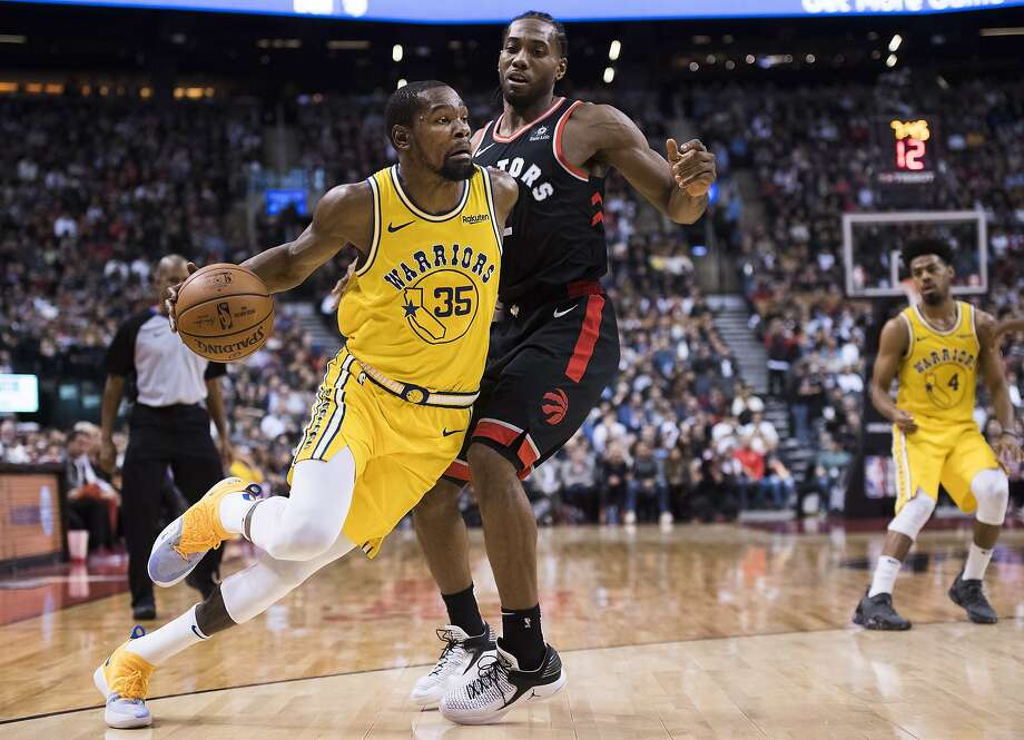 Golden State Warriors forward Kevin Durant (35) drives around Toronto Raptors forward Kawhi Leonard (2) during the second half of an NBA basketball game Thursday, Nov. 29, 2018, in Toronto. (Nathan Denette/The Canadian Press via AP) Photo: Nathan Denette / Associated Press
