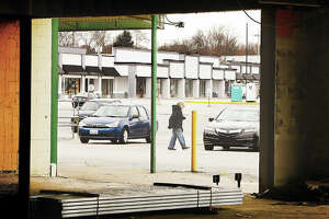 As framed through a gutted out store front at Eastgate Plaza, a Dollar General customer walks to her car Wednesday. Club Fitness will be moving into the space formerly occupied by Illinois Wholesale Furniture, background. The shopping center has been undergoing a massive renovation project which is only partially completed. Workers have gutted the former stores to the bare walls and built them back up, including a new facade.