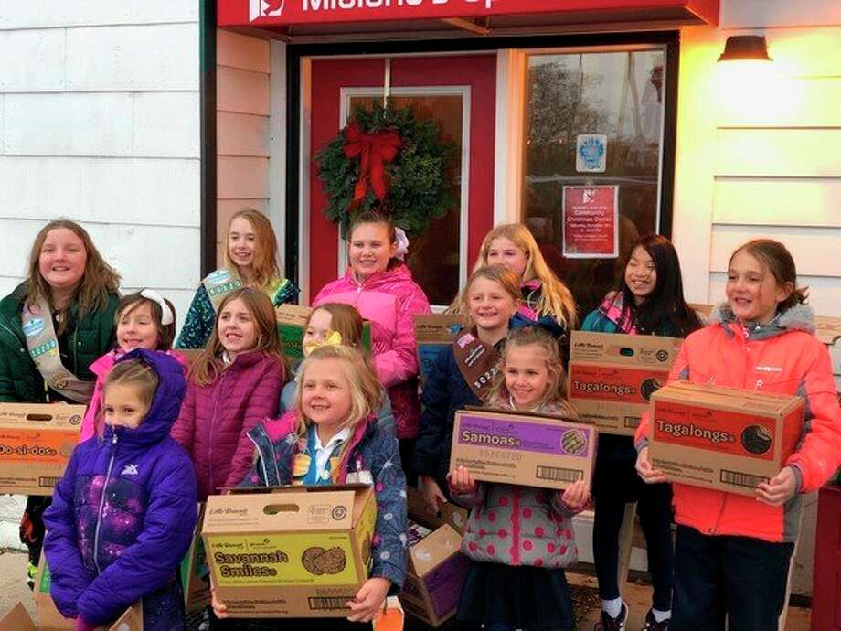 Troop members of Girl Scout Troop 50220 pose with their cookie donations at Midland's Open Door. The troop donated 127 boxes of cookies to be used by the organization to help feed those who use their facilities.