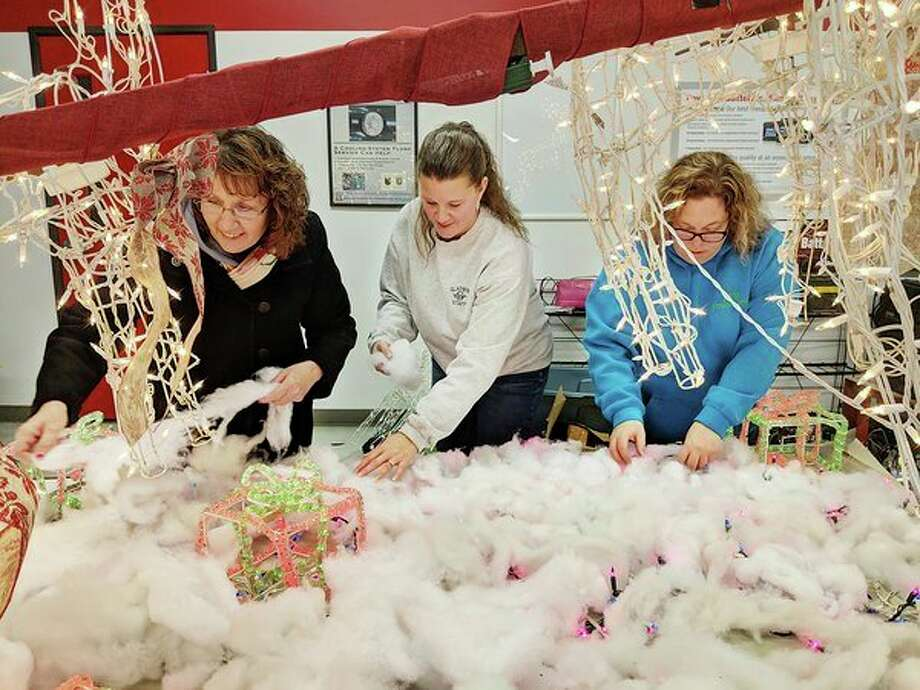 Gladwin County Festival of Lights Christmas Parade Committee members (from left) Lori Stout, Selena Volmering and Kim Bruner work Wednesday at the former Lee Otto Automotive Inc. building on the annual float for the Gladwin Business Professional Association. The group along with committee members Wanda McClain and Shannon Smith-Dorn are retiring from their longtime commitment of overseeing the parade. (Tereasa Nims/For the Daily News)