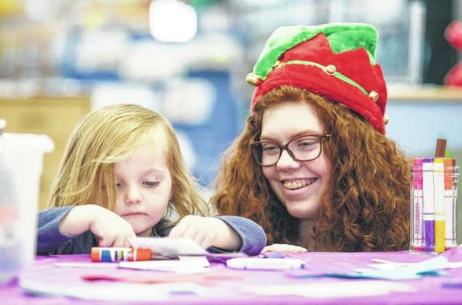 Laura Walker, a sophomore at McCracken County High School in Paducah, Kentucky, is dressed as Junie B. Jones as she helps Bailey Murphy, 3, with Christmas arts and crafts. In partnership with the Class Acts Education Series and the First Stages Mini-Series at the Carson Center, the library hosted a Junie B. party.
