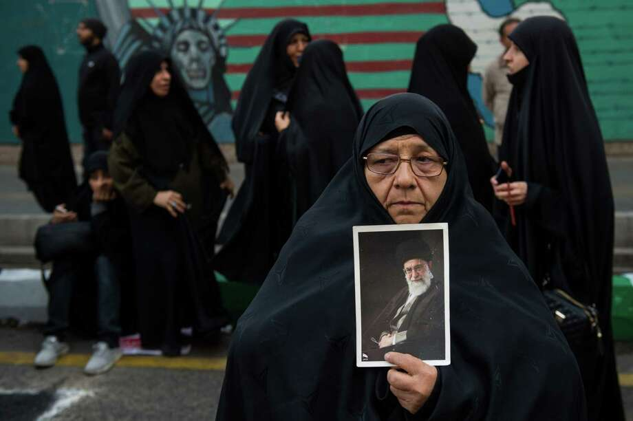 A woman holds a picture of Ayatollah Khamenei, Iran's supreme leader during a demonstration on the anniversary of the U.S. embassy seizure, in Tehran, Iran, on Nov. 4, 2018. Photo: Bloomberg Photo By Ali Mohammadi. / © 2018 Bloomberg Finance LP