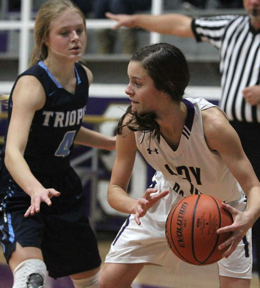 Routt's Kirsten Huffman tries to find an open teammate as Triopia's Chloe Reynolds applies pressure Thursday night.