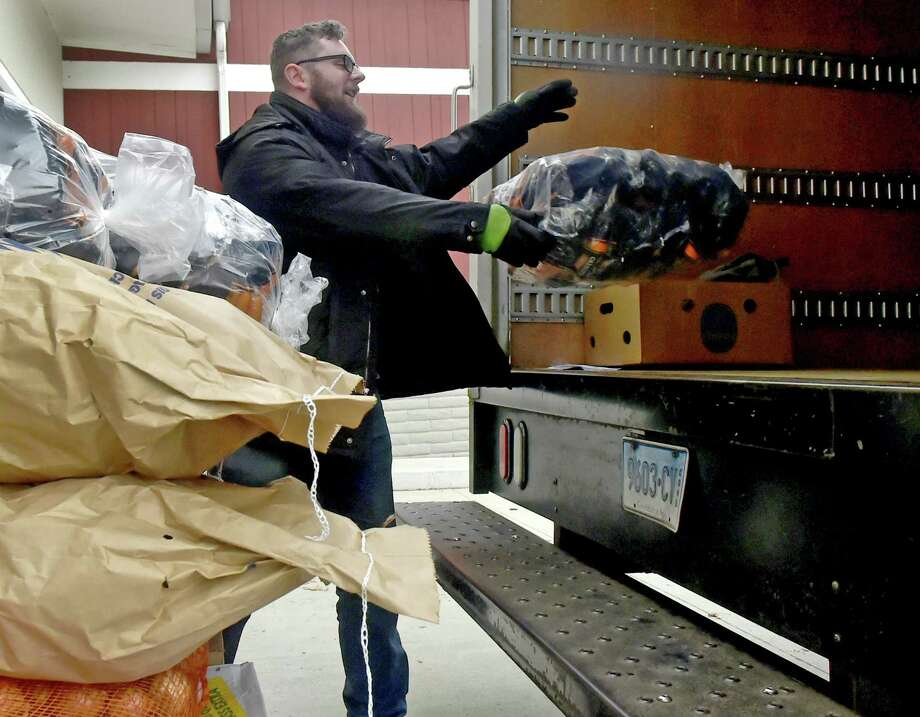 An employee of the Shoreline Soup Kitchen and Pantry program, which serves Old Saybrook, Westbook, Clinton, Old Lyme and Niantic, loads his truck with Thanksgiving food at the Connecticut Food Bank in Wallingford. Photo: File Photo / New Haven Register