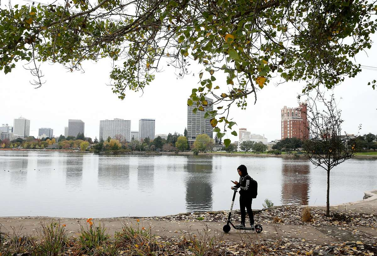 A boy rides a scooter on the path circling Lake Merritt in Oakland, Calif. on Tuesday, Nov. 27, 2018 before rain was expected to dampen the Bay Area.
