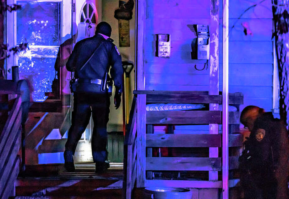 An Alton police officer shines his flashlight into the open door of a residence in the 3400 block of Bolivar Street Thursday night, where authorities responded to what quickly turned into the scene of a homicide investigation. Photo: Nathan Woodside | The Telegraph