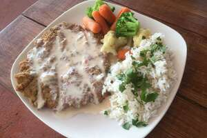 Chicken fried steak ($9.49) topped with queso and sides of cilantro lime rice and mixed vegetables at The Patio Southtown.