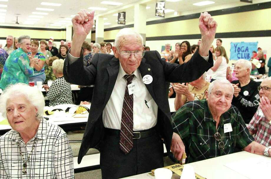 Herbert Lamp raises his hands in celebration as he and other members of the Class of 1943 are honored during the annual alumni breakfast Saturday Sept. 17, 2016, at Conroe High School. Lamp joined RB Kelley, far right, as the oldest alumni - both from the Class of 1943 - at the breakfast at 92 years old. Go to HCNpics.com to view more photos from the event. Photo: Jason Fochtman