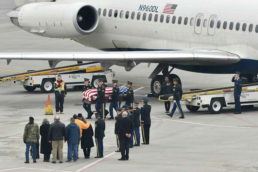 Relatives look on as the remains of Pfc. John Martin, who vanished in North Korea in late 1950, are removed from a Delta airplane at the Albany International Airport on Friday, Nov. 30, 2018 in Colonie, N.Y. His great, great nephew Airman 1st Class Schuyler Dolton is seen saluting at far right. On Sunday, the 68th anniversary of his disappearance and likely combat death during the Korea War, he will be buried next to his mother and father after a funeral in Schuylerville. (Lori Van Buren/Times Union)