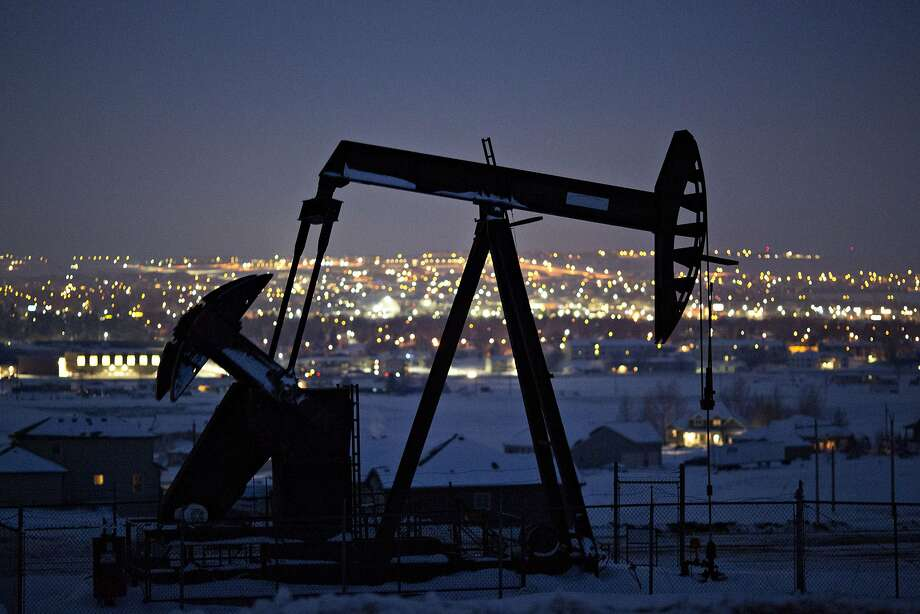 A pumpjack operates above an oil well at night in the Bakken Formation on the outskirts of Williston, North Dakota. Photo: Daniel Acker, Bloomberg