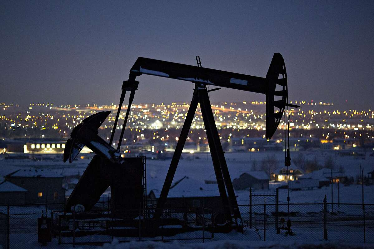 A pumpjack operates above an oil well at night in the Bakken Formation on the outskirts of Williston, North Dakota.