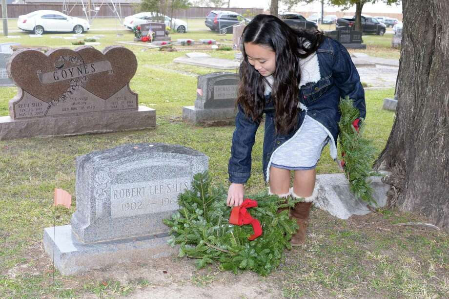 Katelyn Nitsche of Girl Scout Troop 17384 lay wreaths on veterans' graves during the Wreaths Across America Ceremony at the Magnolia Cemetery in Katy on Saturday, Dec. 16, 2017. Photo: Craig Moseley, Staff / Houston Chronicle / ©2017 Houston Chronicle