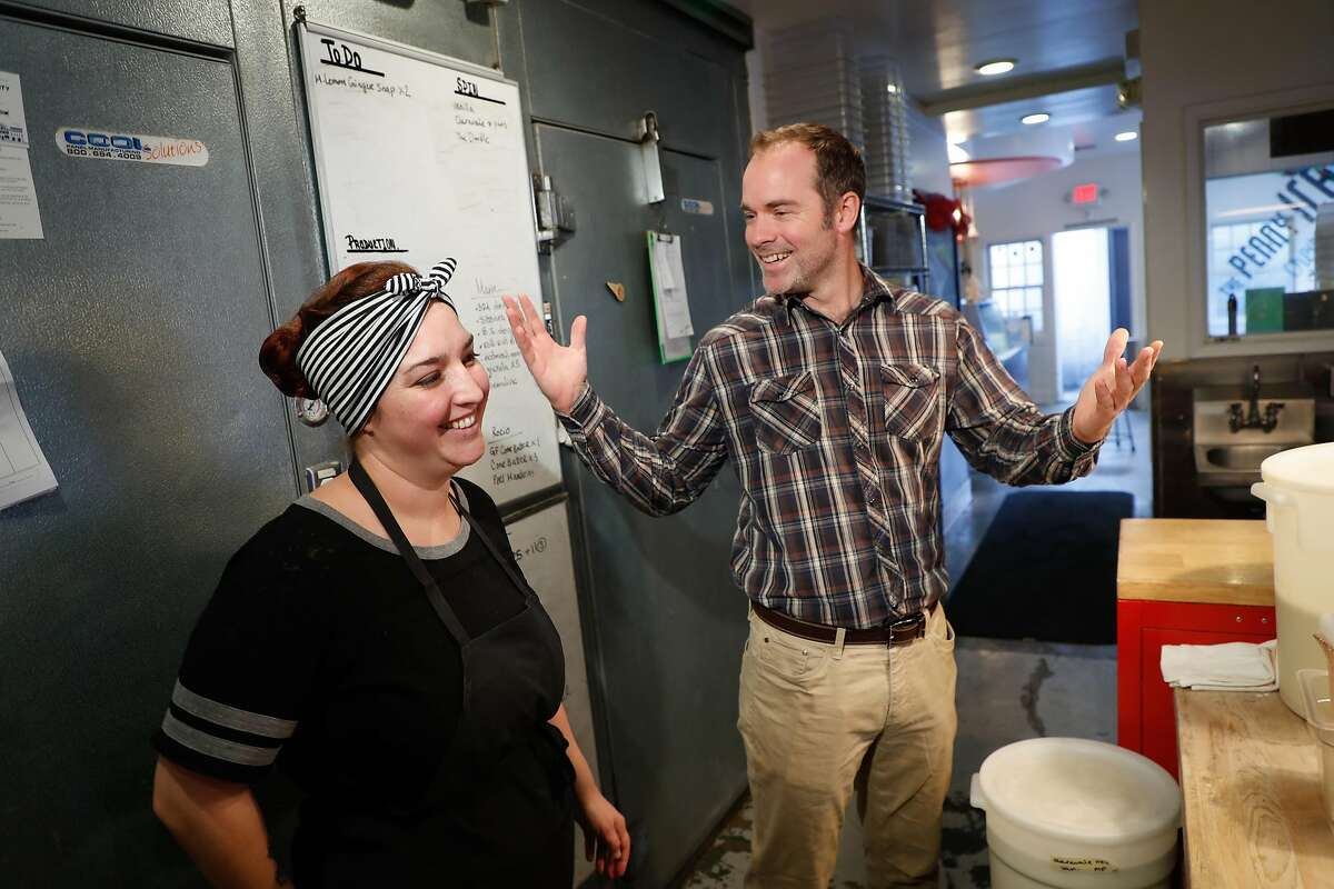 Owner Zachary Davis, at right, talks with employee Monique Plossl in the kitchen at Penny Ice Creamery on Friday, Nov. 30, 2018, in Santa Cruz, Calif. Owner Zachary Davis is a small employer participating in Cal Savers, a state-run retirement program for employers who do not offer their own plan.